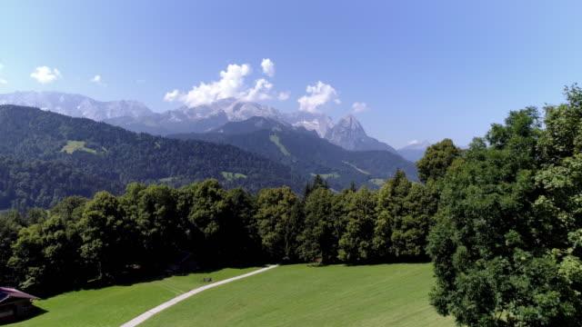vídeos de stock, filmes e b-roll de montanhas wetterstein com monte zugspitze visto de pastagem alpina - montanha zugspitze