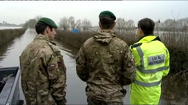 wettest january on record / flooding in somerset; england: somerset: ext two soldiers along with member of local authority and press to look at... - major road video stock e b–roll