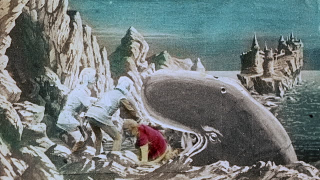 1903 Whale spits adventurers onto on rocky coast, and they follow goddess into cave during the film, Le Royaume des fées (The Kingdom Of Fairies) by Georges Melies