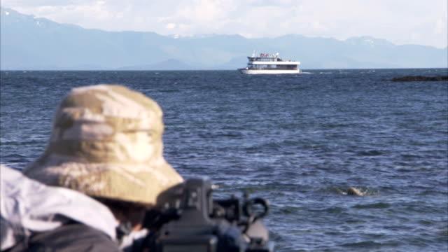 vídeos y material grabado en eventos de stock de a whale watcher adjusts his camera. - cetáceo