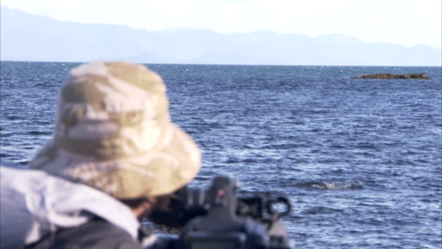 a whale watcher peers through his video camera as a whale fin breaks the surface. - whale watching stock videos & royalty-free footage