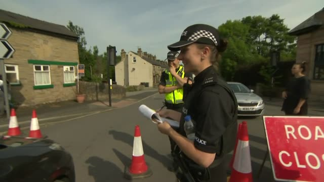 Residents leave homes / police road blocks / Chinook helicopters working to repair dam ENGLAND Derbyshire Whaley Bridge EXTVarious of police officers...