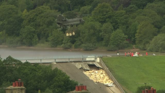 Residents leave homes / police road blocks / Chinook helicopters working to repair dam ENGLAND Derbyshire Whaley Bridge EXTChildren watching RAF...
