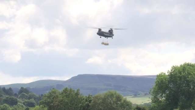 Thousands evacuated from town as dam at risk of bursting ENGLAND Derbyshire Whaley Bridge EXT Various shots of helicopter carrying sandbags