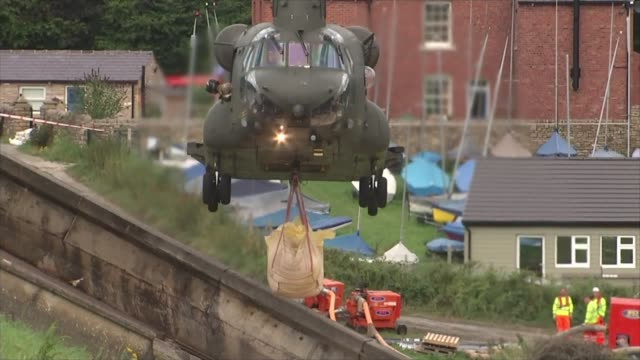 Thousands evacuated from town as dam at risk of bursting ENGLAND Derbyshire Whaley Bridge EXT Nose view of RAF Chinook depositing sandbags on dam...