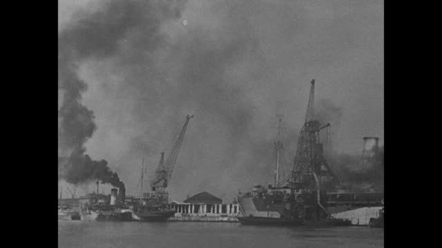 WS wharf and supply depot probably in England cranes outlined against sky dark smoke rising airships in sky / view of wharf from moving boat / boxes...