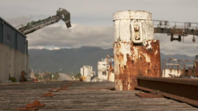 vídeos de stock, filmes e b-roll de wharf area in westport with rusty rail tracks vessell and beacon on breakwater - quebra mar