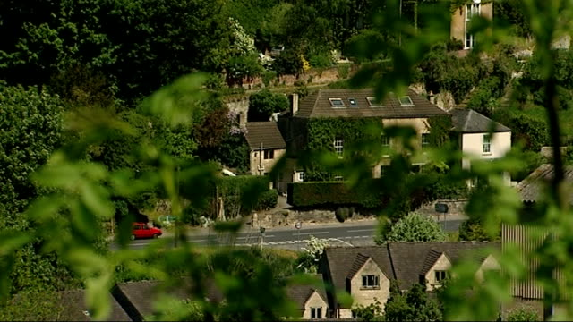 vídeos y material grabado en eventos de stock de what would you cut / value added tax fraud england gloucestershire cotswolds stroud ext rooftops of houses seen from behind trees reporter to camera - cotswolds