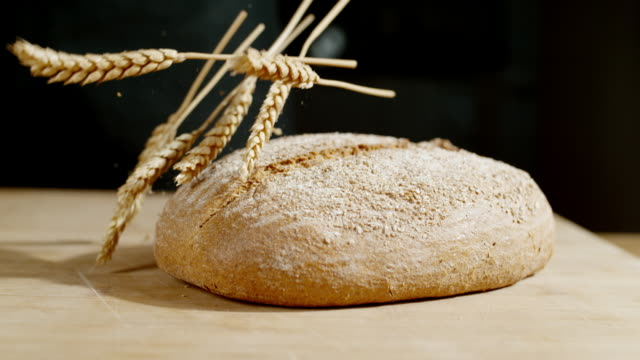 slo mo wheat ears falling on a round bread - bread stock videos & royalty-free footage