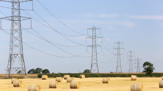 Wheat stubble in a field on Yorkshire's East Coast, UK, with high voltage power lines from a coal fired power station.
