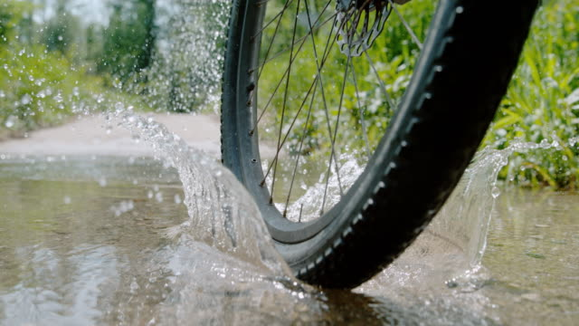 vídeos de stock e filmes b-roll de slo mo cu wheel of a mountain bike splashing the puddle - poça