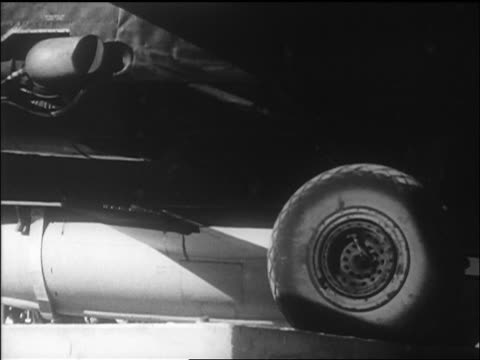 B/W 1947 wheel of B29 with Yeager's Bell X1 airplane taxiing on airfield / California / newsreel