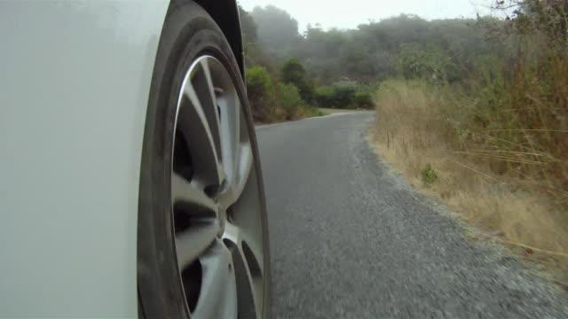 CU POV SLO MO Wheel of car turning around corners of country road / Big Sur, California, USA