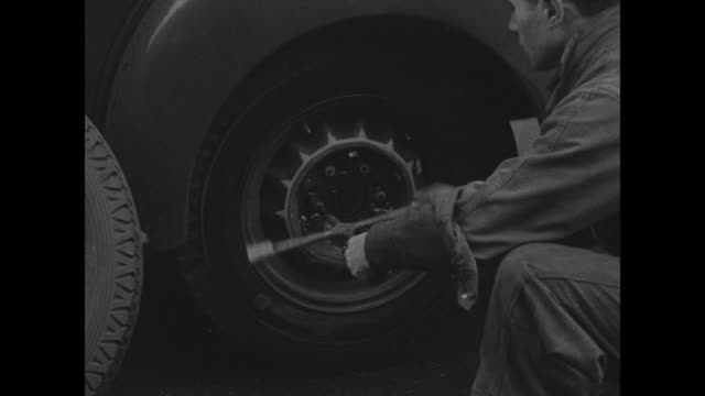 wheel of truck as mechanic crouched screen right applies lug wrench, tightens lugs, replaces hubcap, stands up and rolls old tire out of frame,... - wrench stock videos & royalty-free footage