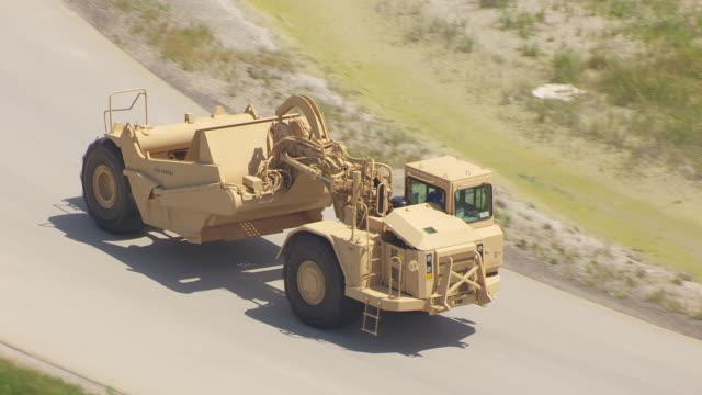 vidéos et rushes de ms ts aerial pov wheel tractor-scraper moving on road for test driving at caterpillar plant / decatur, illinois, united states - essai de voiture