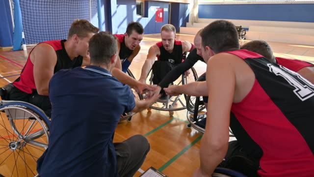 wheelchair basketball team cheering with stacked hands - wheelchair basketball stock videos & royalty-free footage
