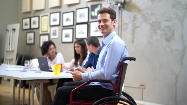 vídeos de stock, filmes e b-roll de retrato de homem de negócios de cadeira de rodas no local de trabalho - cadeira de rodas equipamento ortopédico