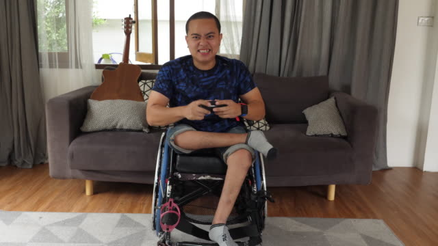 wheelchair disabled man playing video game in house - wheelchair stock videos & royalty-free footage