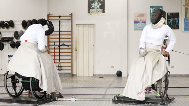 Wheelchair fencing athletes dueling