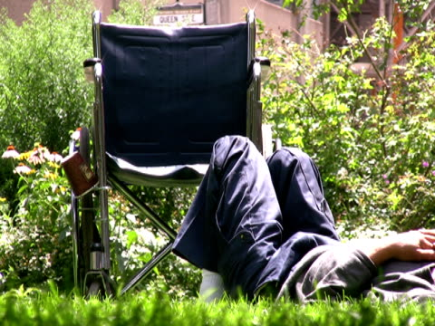 stockvideo's en b-roll-footage met wheelchair man resting in park as world passes by - achterover leunen