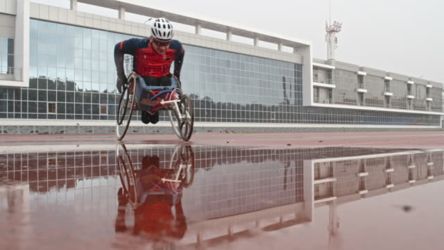 wheelchair racer going through puddle - track and field event stock videos & royalty-free footage