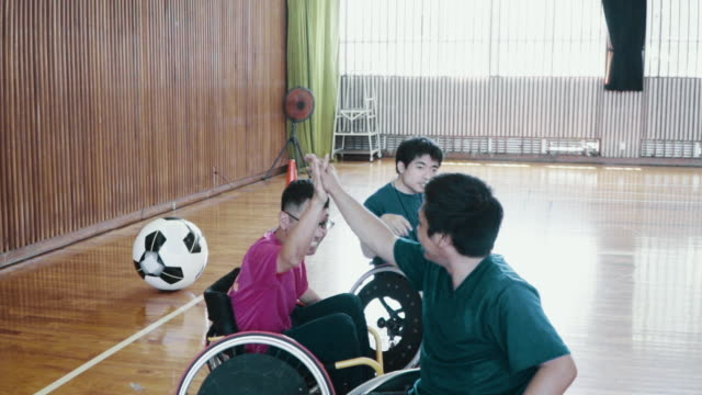 wheelchair soccer athletes celebrating victory after a goal - motivation stock-videos und b-roll-filmmaterial