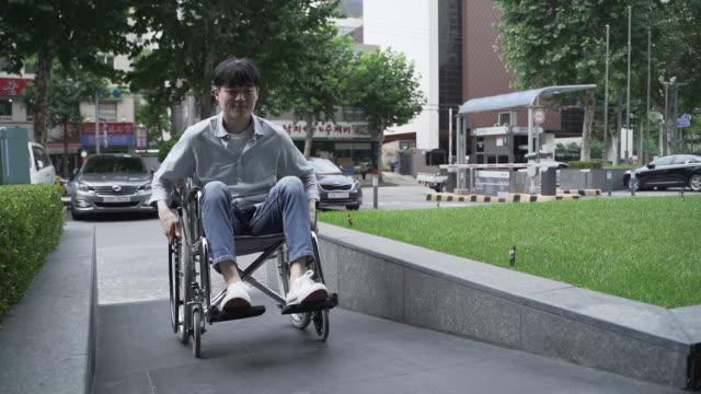 vidéos et rushes de wheelchair user moves up a ramp - vie citadine