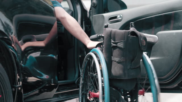 wheelchair with a disabled person is get out of a car - polio stock videos & royalty-free footage