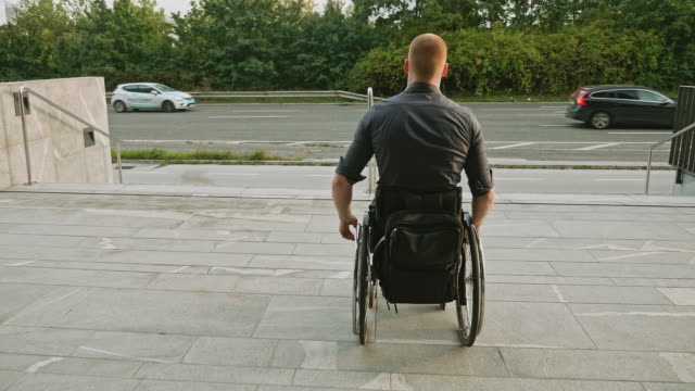 wheelchair-bound businessman faces inaccessible stairs - prejudice stock videos & royalty-free footage