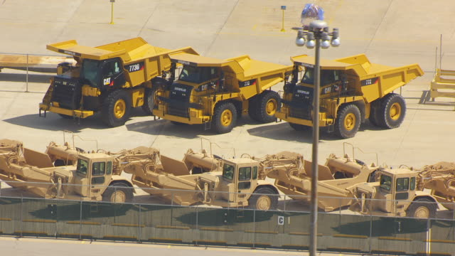 ws aerial pov wheeled tractor-scrapers and dump trucks parked at caterpillar plant / decatur, illinois, united states - fleet of vehicles stock videos and b-roll footage
