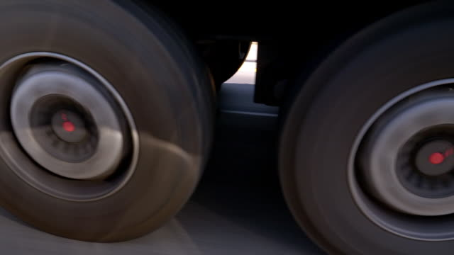 wheels of a semi-truck rolling on highway - moving past video stock e b–roll