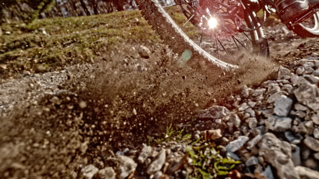 slo mo wheels of the mountain bike pushing gravel into the air in sunshine - gravel stock videos & royalty-free footage