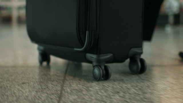 CU of wheels on suitcase pushed by man in airport