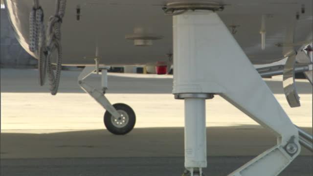 wheels on the landing gear of an aircraft roll across a tarmac. - landefahrwerk stock-videos und b-roll-filmmaterial