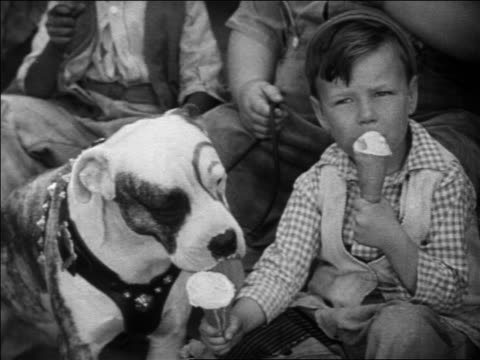 stockvideo's en b-roll-footage met b/w 1931 wheezer with pete the pup from our gang sitting + eating ice cream cones / feature - 1930