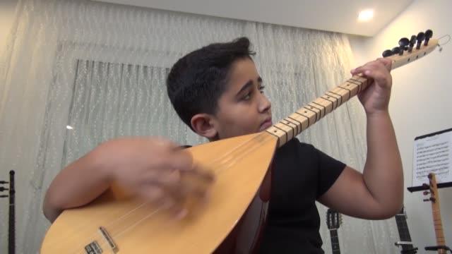 stockvideo's en b-roll-footage met when his father was struggling to play cura – a stringed musical instrument – baby fingers of four-year-old eren yavuz, were striking notes like an... - beeldtechniek