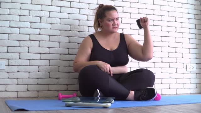 vídeos y material grabado en eventos de stock de cuando thai grande construir mujer en telas de ejercicio ver un equilibrio de peso, que quiere romper por martillo - piel grasa