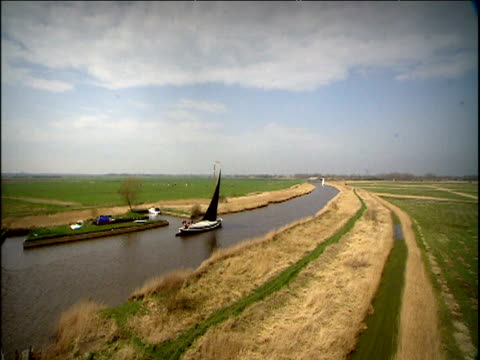 wherry sailing on broads past freshly harvested fields norfolk - menschliche gliedmaßen stock-videos und b-roll-filmmaterial