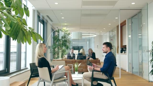 ビジネスマンが仕事のために女性にインタビューしている間、他の人は隣のオフィスで会議をしています - フリーアドレス点の映像素材/bロール