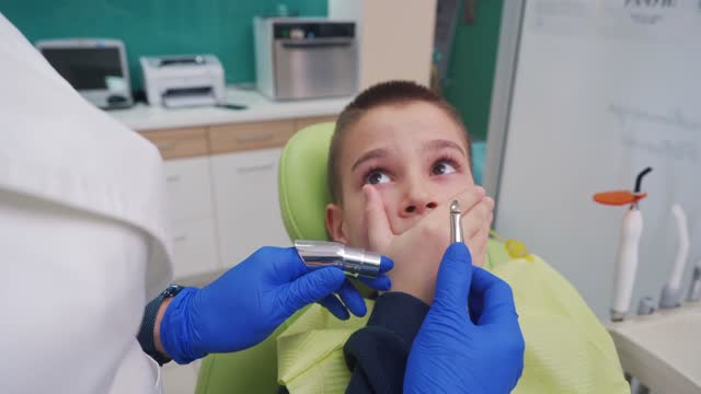 while covering his mouth with a hand, worried boy won't cooperate for his tooth extraction procedure - 10 11 years stock videos & royalty-free footage