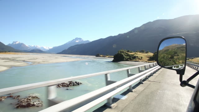 pov while driving along road past mountain ranges - new zealand stock videos & royalty-free footage