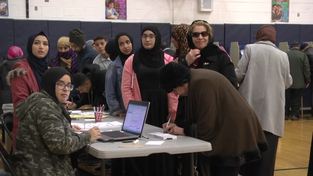 while helping a group ofarabamerican voters sign in to cast their ballots a poll worker asks the cameraman who he works for - dearborn michigan stock videos & royalty-free footage