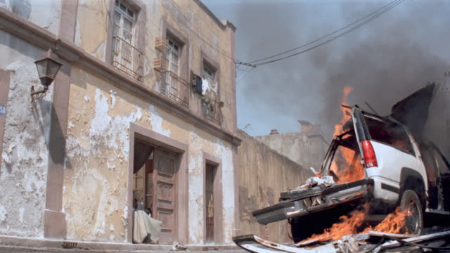 while the wreckage of one chevy suv burns, another suv backs into it. - entrare in collisione video stock e b–roll