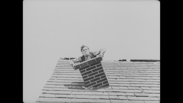 1920 While trying to place a chimney on the house, man (Buster Keaton) falls through the roof and into a bathtub full of water