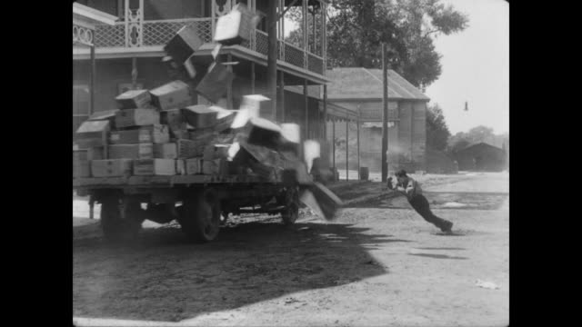 1928 while trying to run against the wind, a pile of boxes is blown onto a man (buster keaton) - 1928 stock videos & royalty-free footage