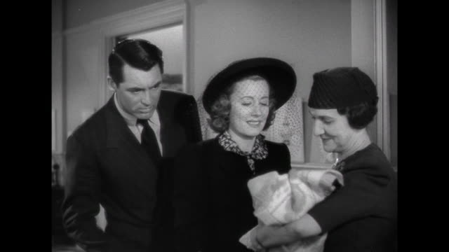 1941 while visiting an adoption nursery, wife (irene dunne) is more taken by a baby girl than is father (cary grant) - adoption stock videos & royalty-free footage