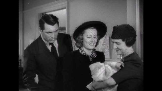 vídeos y material grabado en eventos de stock de 1941 while visiting an adoption nursery, wife (irene dunne) is more taken by a baby girl than is father (cary grant) - orfanato