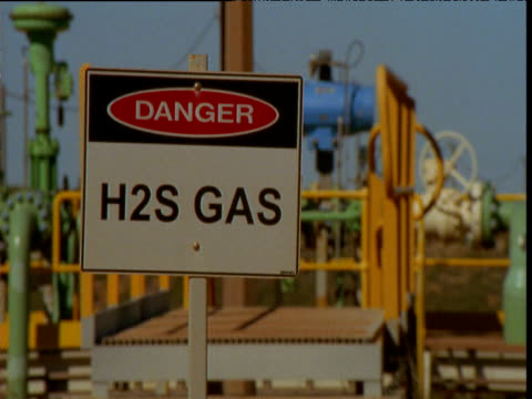Whip pan between 'hydrogen sulphide' and 'restricted area' warning signs at oil refinery, Barrow Island, Western Australia