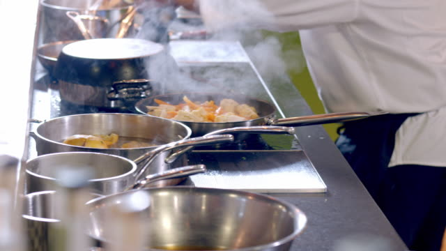 whip pan from judges to pans and skillets steaming from boiling foods in chef challenge cooking competition as chef adds a chunk of butter to one of the pots on stove - contestant stock videos and b-roll footage
