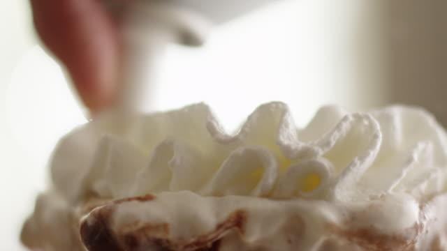 whipped cream swirl sprayed onto top of ice cream sundae in parfait glass - サンデー点の映像素材/bロール